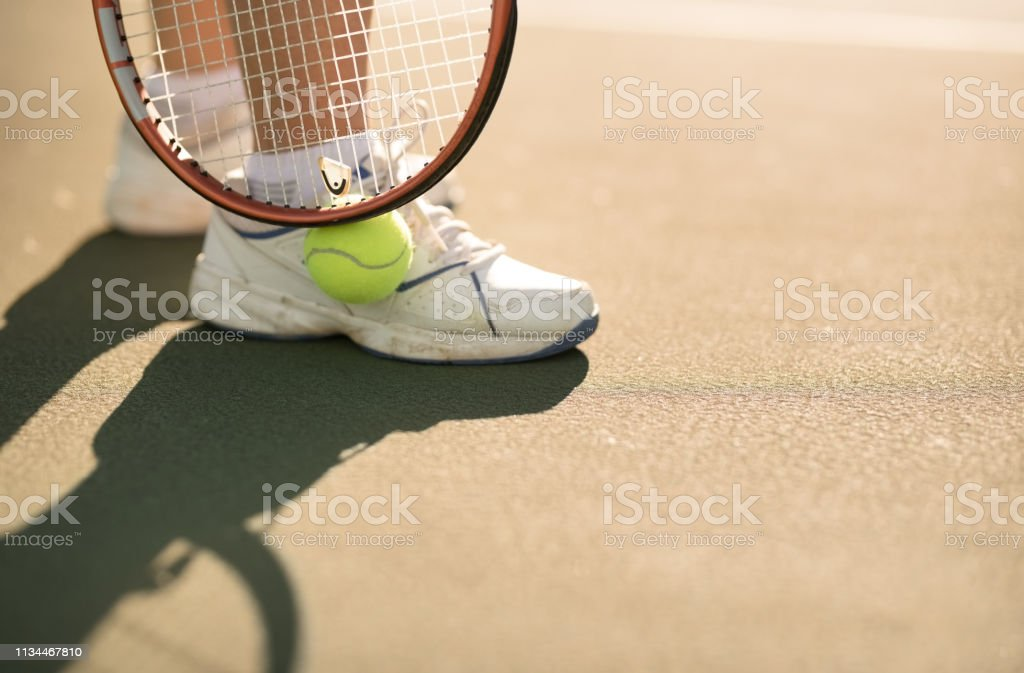Close up shot of feet of a woman standing on tennis court with ball...