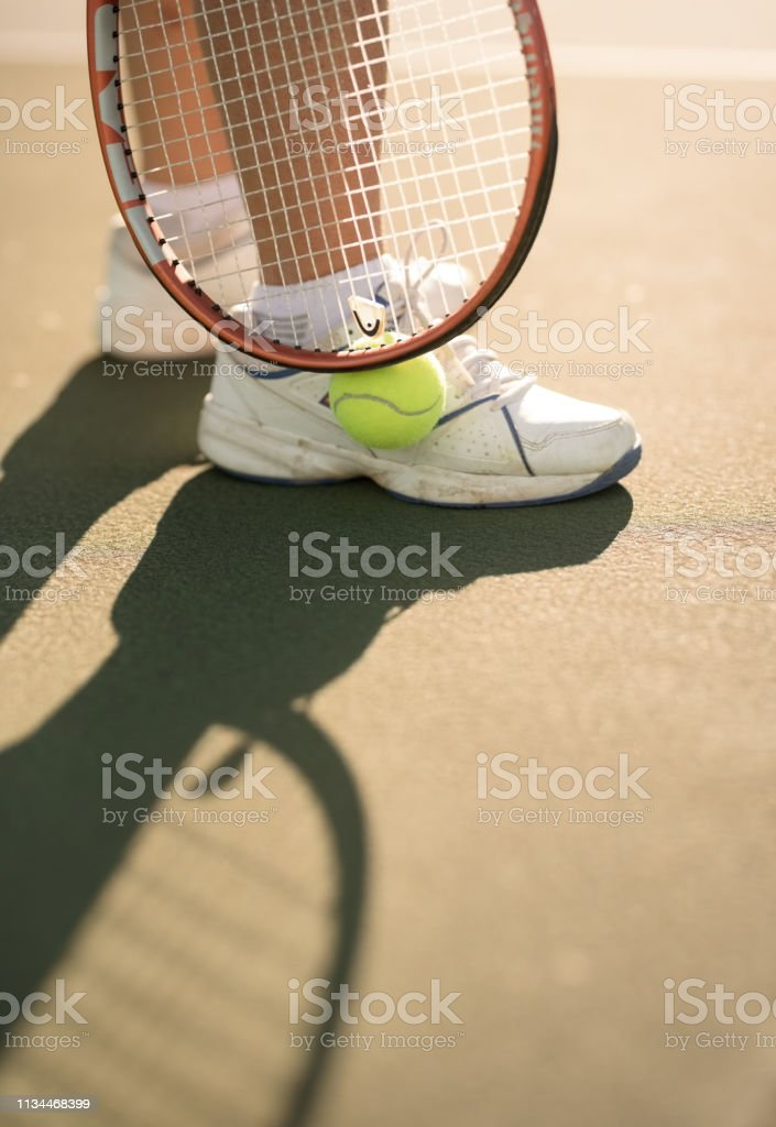 Close up of feet of a woman standing on tennis court with ball and...