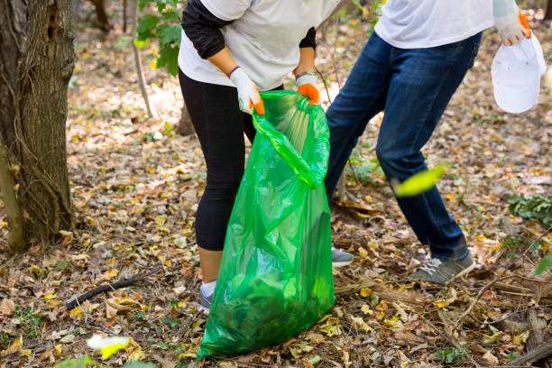 Picking up trash in the forest Picking up trash in the forest. Ecology people cleaning the park with green garbage bag. Unrecognizable people. environmental cleanup stock pictures, royalty-free photos & images