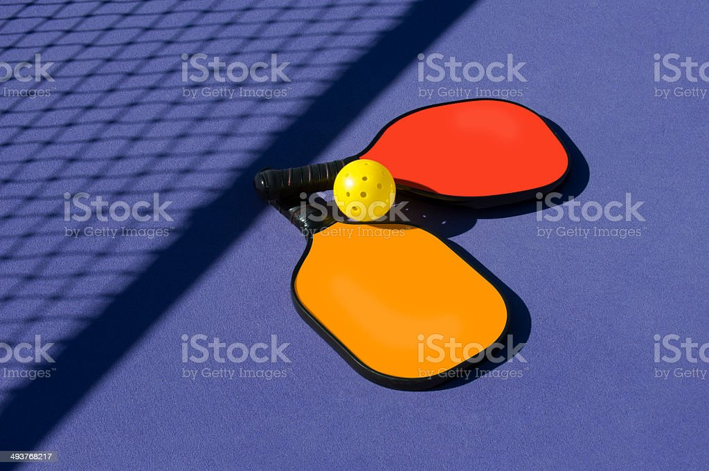 Pickleball - 2 paddles and ball sitting near net shadow stock photo