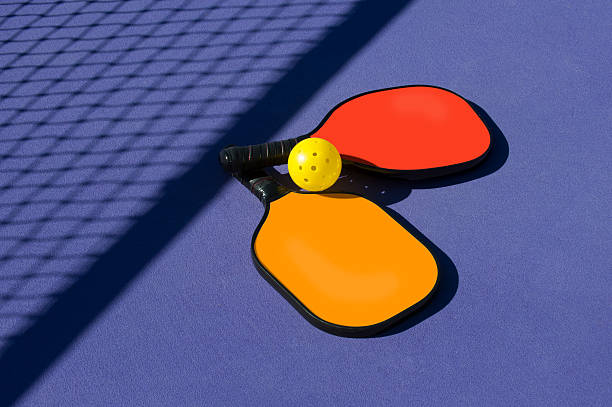 pickleball - 2 paddles and ball sitting near net shadow - table tennis racket stock pictures, royalty-free photos & images