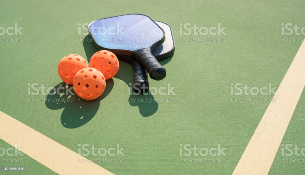 Pickleball and paddle on court stock photo