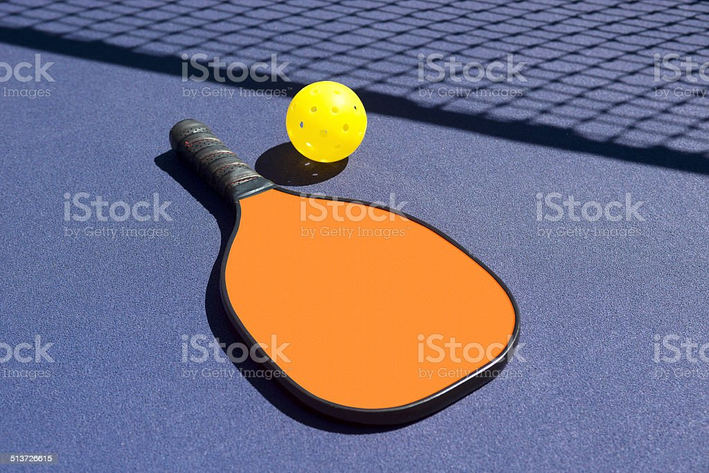 Pickleball - Orange Paddle Yellow Ball Net Shadow stock photo