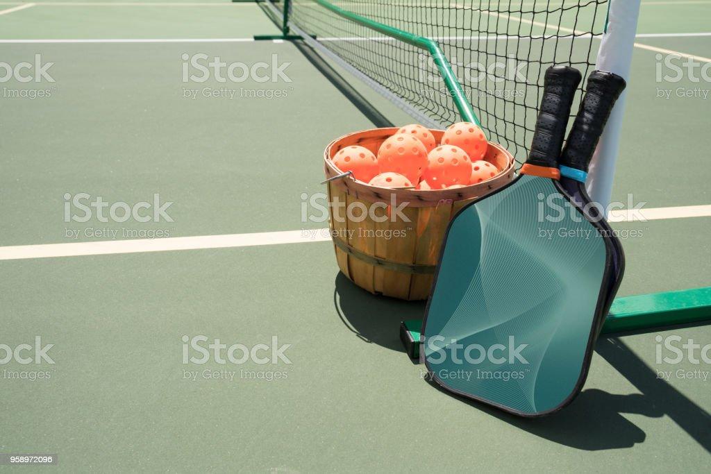 Pickleball Paddel und Kugeln durch Netz. – Foto