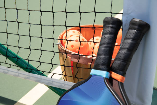 Pickleball paddle and balls by net. stock photo