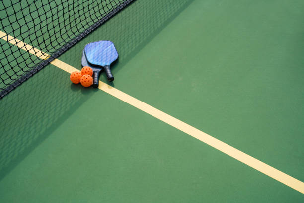 pickleball paddles and ball in shadow of net - racket sport stock pictures, royalty-free photos & images