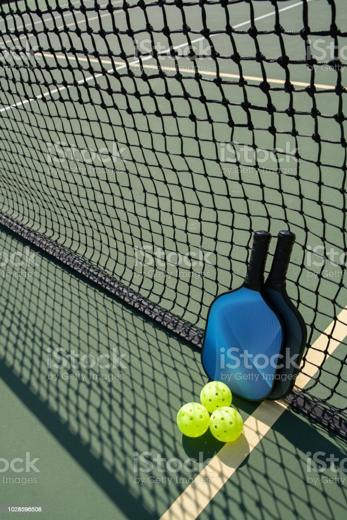 Pickleball paddles and ball on court with shadow of net ++graphics on...