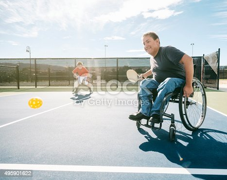 Two young men playing the game of pickleball on a court. One of the men is in a wheelchair. Horizontal composition with sunlight behind the players.