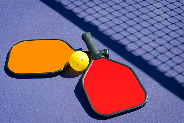 pickleball - two paddles and a ball in net shadow - table tennis racket stock pictures, royalty-free photos & images