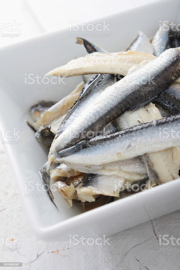 pickled anchovies in white dish stock photo