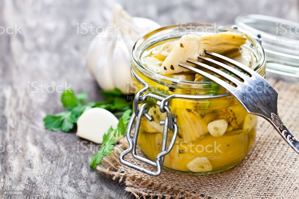 Pickled  artichoke with garlic in a glass jar on rustic wooden table - foto stock