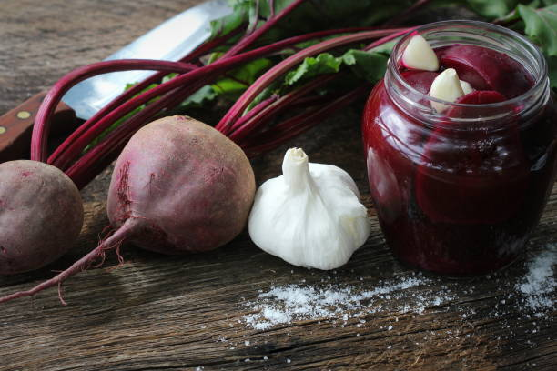 Pickled beets in the jar on a dark wood background stock photo