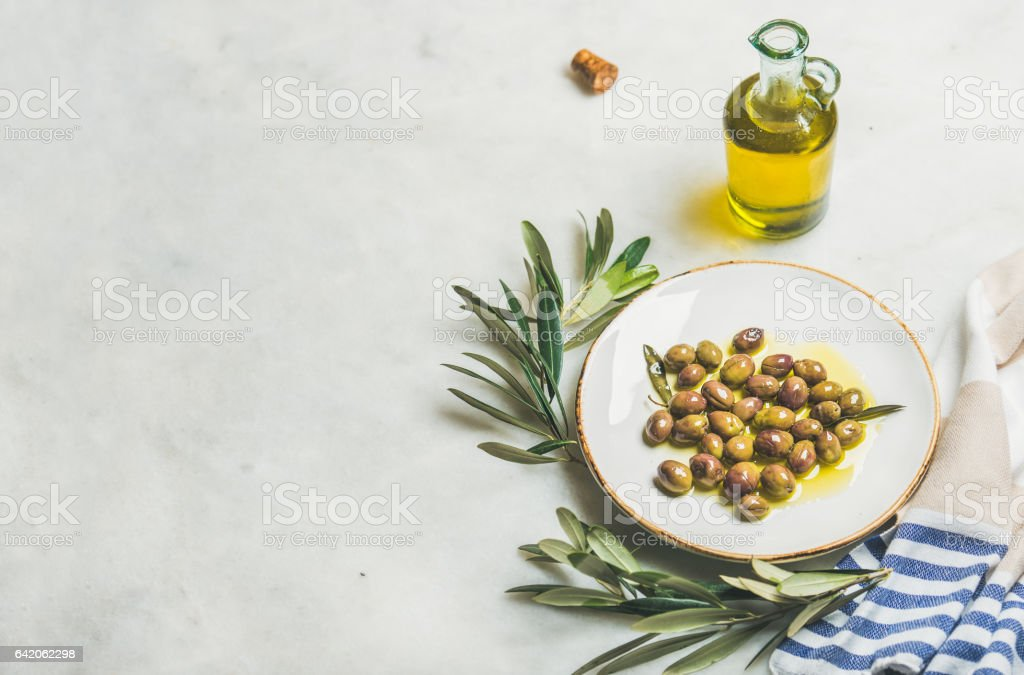 Pickled green Mediterranean olives, olive tree branch and oil stock photo