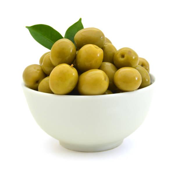 eingelegte grüne oliven in eine schüssel geben und olive ast auf weißem hintergrund - schwarze olive stock-fotos und bilder