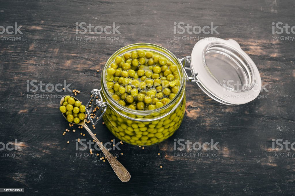 Pickled green peas in a jar. Stocks of food. Top view. On a wooden background. Copy space. - Royalty-free Bean Stock Photo