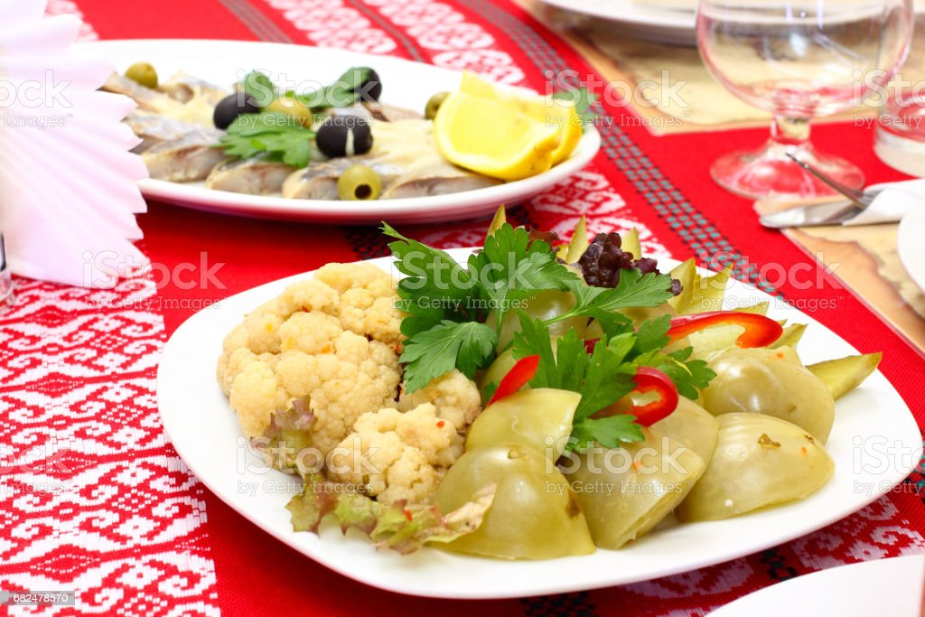Pickled green tomatoes and pickled cauliflower sliced and decorated with parsley and red bell pepper in a white plate on a red tablecloth embroidered Ukrainian national ornament. Ukrainian traditional dish royalty-free stock photo