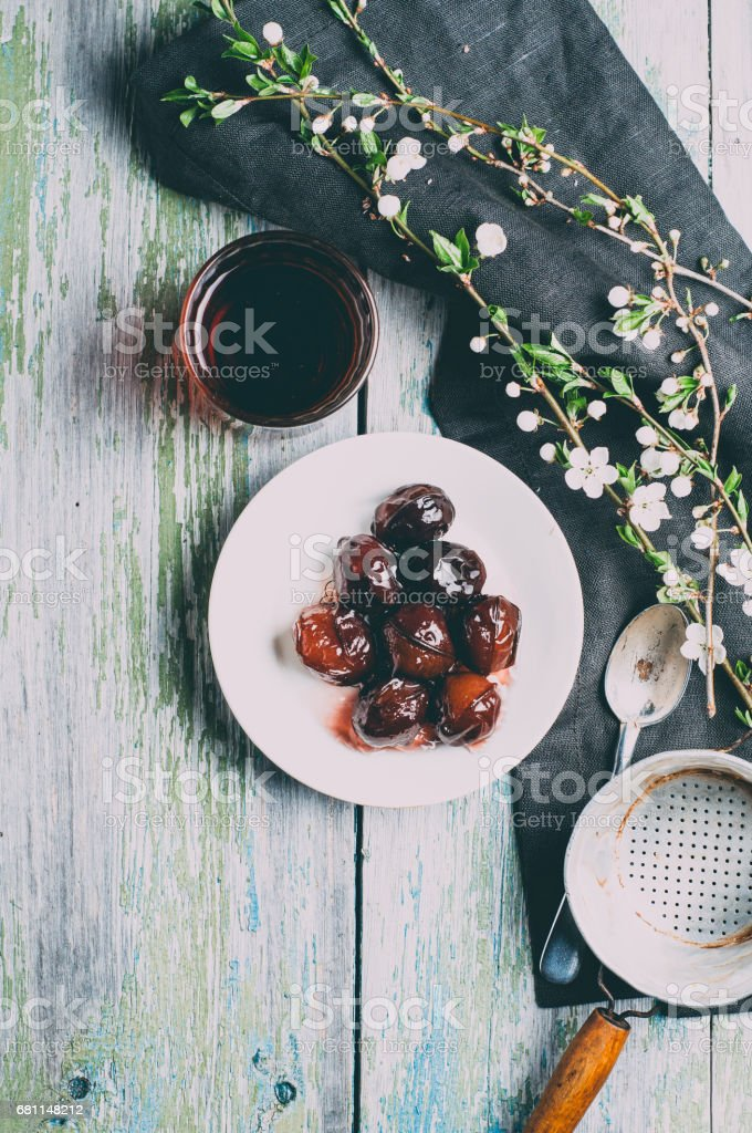 Pickled plum on a white plate over old wooden table stock photo