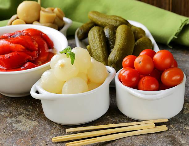 eingelegt snacks (tapas)-pilzen und tomaten, gurken - perlzwiebeln stock-fotos und bilder