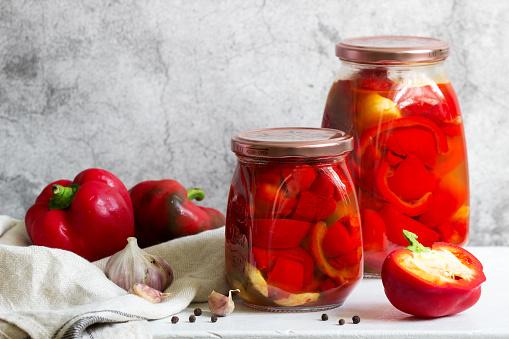 Pickled sweet peppers in glass jars on a light surface. Selective focus.