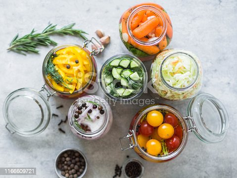 Pickled vegetables. Salting various vegetables in glass jars for long-term storage. Preserves vegetables in glass jars. Variety fermented green vegetables on table.