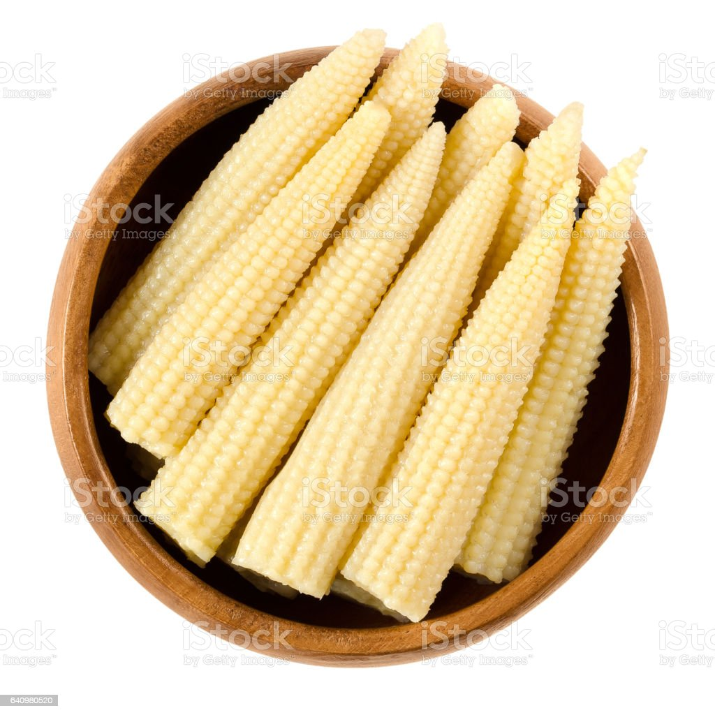 Pickled whole baby corn in wooden bowl over white stock photo