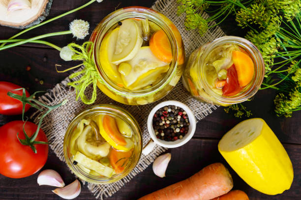 Pickles: vegetable assortment (zucchini, pepper, carrots, tomato, green peas) in glass jars on a dark wooden background. The top view stock photo