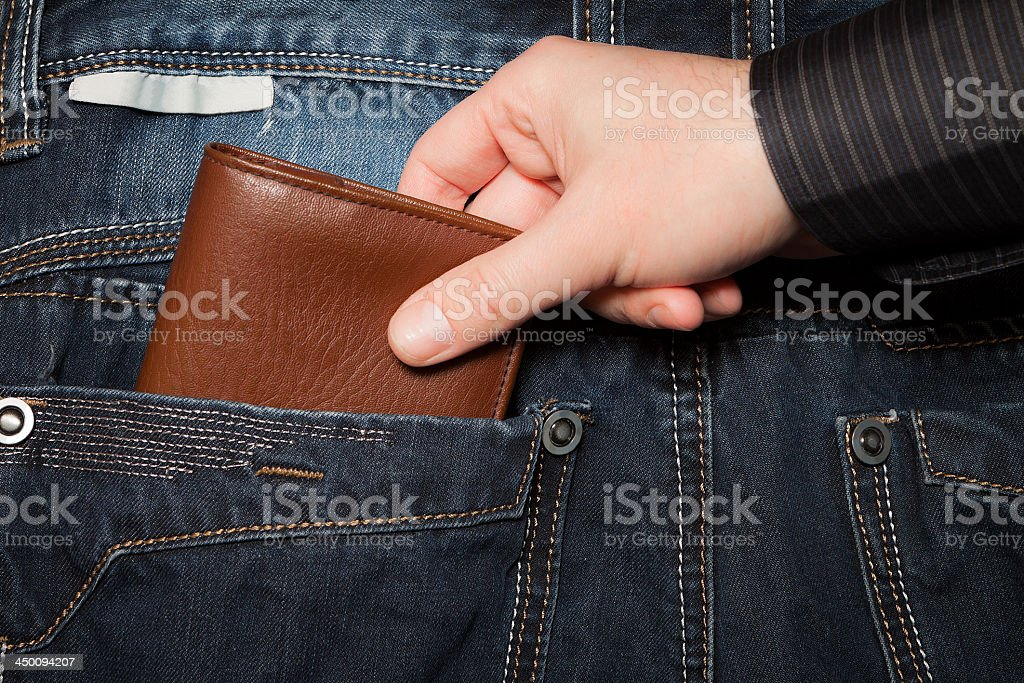 A pickpocket stealing a brown wallet from a back pocket stock photo