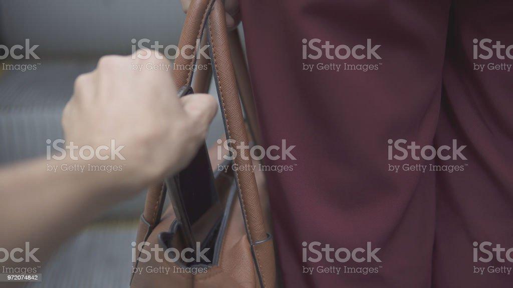 Taschendieb Dieb stiehlt Smartphone von orange Handtasche – Foto