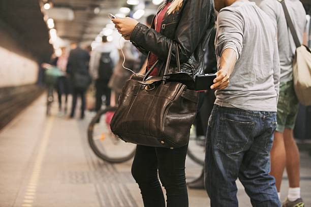 Pickpocketing at the subway station Thief stealing wallet from purse of a woman using mobile phone at the subway station. Pickpocketing at subway station thief stock pictures, royalty-free photos & images