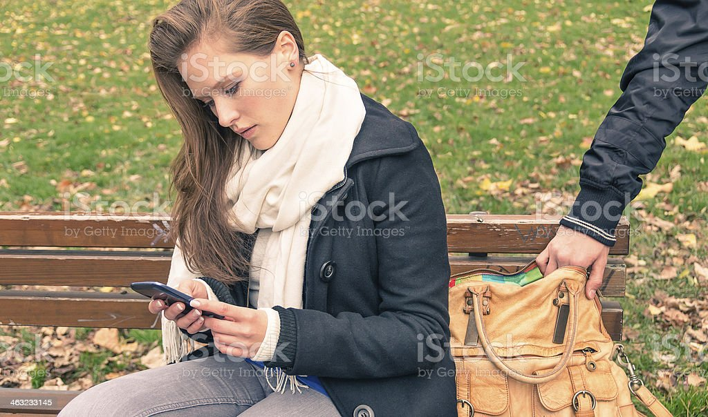 Pickpocketing from the bag of a young woman outdoors stock photo