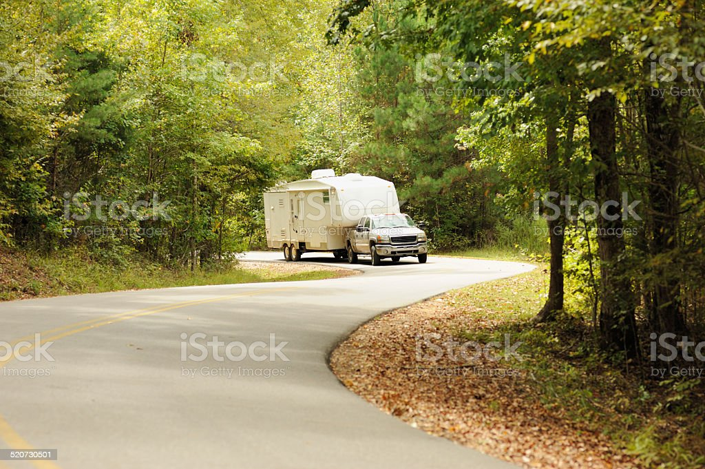Pickup truck and rv on winding road stock photo