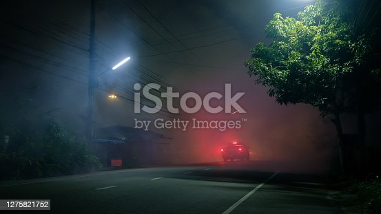 istock Pickup truck drive into fog on empty road with red taillight in silent town 1275821752