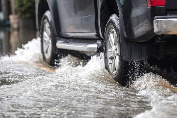 camionnette dans une rue inondée - pluie photos et images de collection