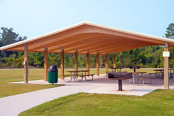 Picnic area Picnic tables and grill under wood roof structure in local park pavilion stock pictures, royalty-free photos & images