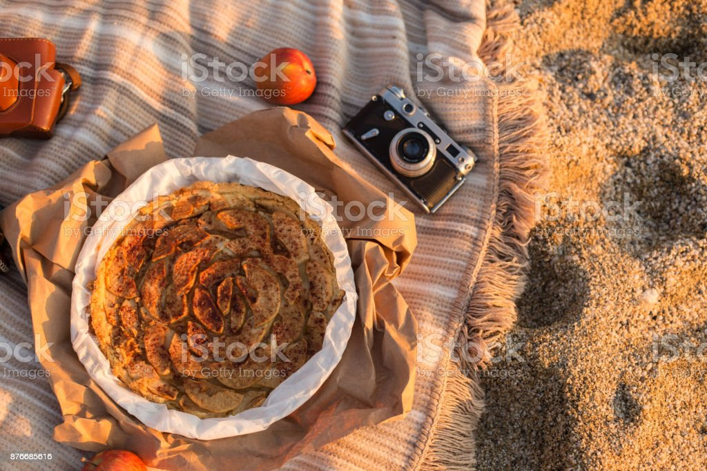 Picnic at the beach. Flat lay with apple pie, apples and vintage stock photo