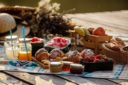 Picnic at the park. Fresh fruits, ice cold sparkling drinks and croissants on a hot summer day. Picnic lunch. selective focus.
