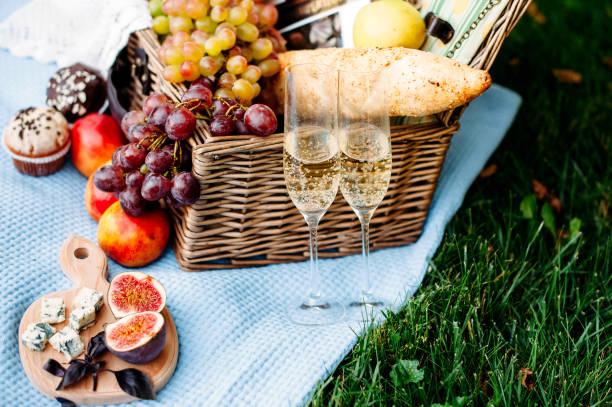 picknick im park auf einer wiese, leckeres essen: korb, wein, trauben, pfirsiche, baguette, cupcakes, feigen, käse, tblue tischdecke, gläser mit champagner - romantisches picknick stock-fotos und bilder