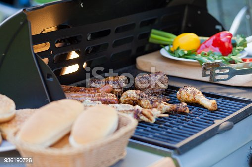 BBQ with different meat, chicken, sausage, hot-dog, souvlaki and more. Bread and vegetables by the side.