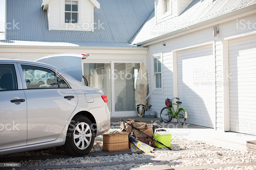 Picnic basket, fishing rod, flippers and bags outside car in driveway stock photo