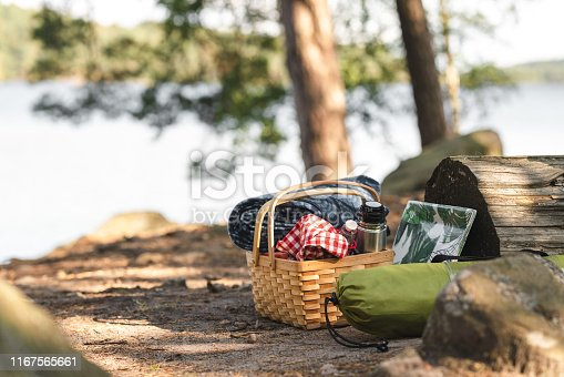 A tent and a picnic basket is waiting to be unpacked in a forest.