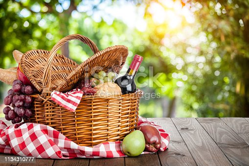 Three quarters front view of a picnic basket shot on a wooden table against defocused lush foliage. Predominant colors are brown, red and yellow. The basket is filled with bread, cheese, grapes, and salami. Out of the basket are some fruits. The composition is at the left of an horizontal frame leaving useful copy space for text and/or logo at the right. High key DSRL outdoors photo taken with Canon EOS 5D Mk II and Canon EF 100mm f/2.8L Macro IS USM.