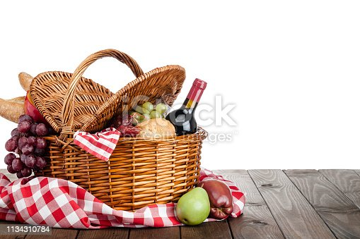 Three quarters front view of a picnic basket shot on a wooden table against white background. Predominant colors are brown and white. The basket is filled with bread, cheese, grapes, and salami. Out of the basket are some fruits. The composition is at the left of an horizontal frame leaving useful copy space for text and/or logo at the right. High key DSRL outdoors photo taken with Canon EOS 5D Mk II and Canon EF 100mm f/2.8L Macro IS USM.