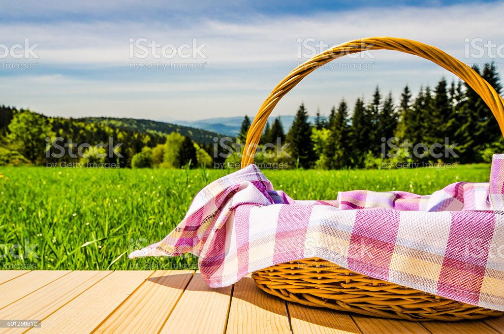 Picnic basket on wooden table stock photo