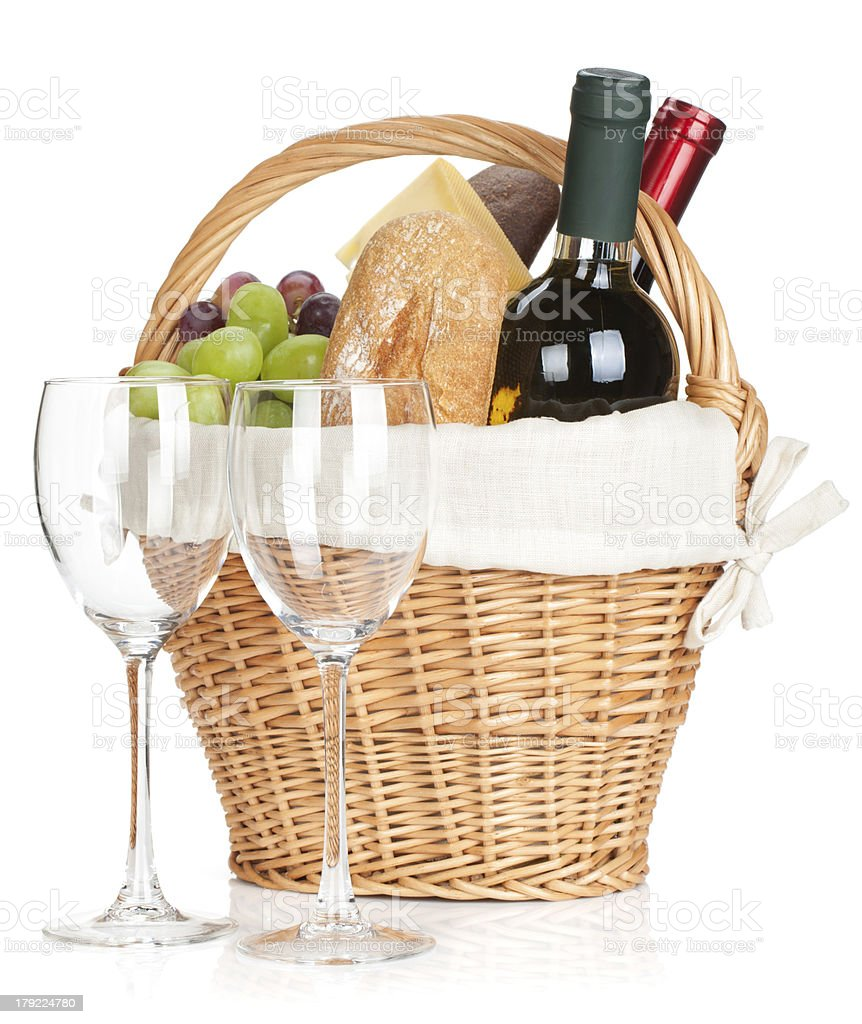 Picnic basket with bread, cheese, grape and wine bottles royalty-free stock photo