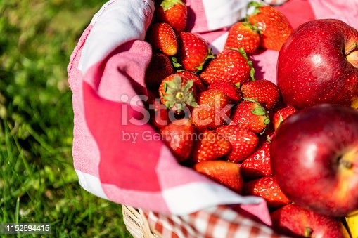 Picnic basket with choice of organic fruits arranged on green grass in park. Fresh apples and strawberries inside of picnic basket.