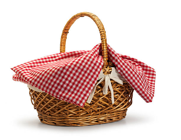 Picnic basket with red checkerboard tablecloth on white background stock photo