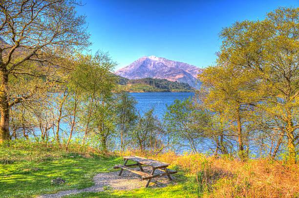 picnic bench seat loch leven scotland snow topped mountains - see loch leven stock-fotos und bilder
