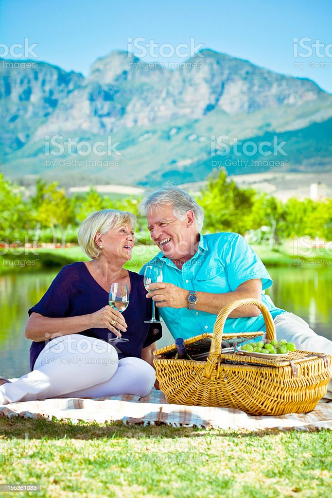 Picnic by the lake Happy senior couple having picnic by the lake with beautiful mountains view in the background. 65-69 Years Stock Photo