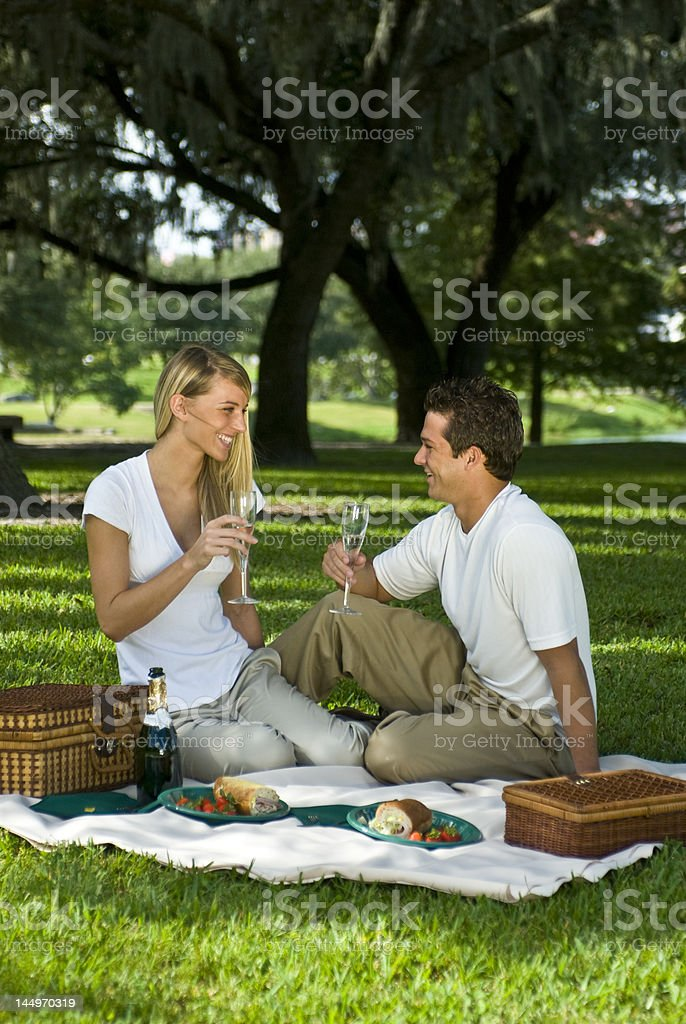 Picnic Couple in lush green city park royalty-free stock photo