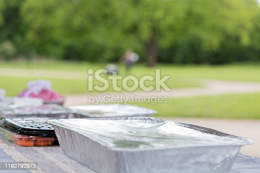 A picnic table set with picnic foods ready and prepared for guests.